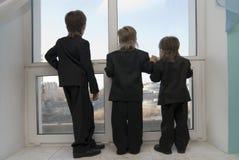 De kinderen kijken in een venster royalty-vrije stock foto