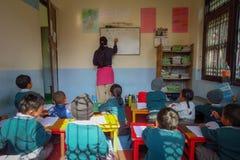 De kinderen in klaslokaal, leraar schrijft op whiteboard, Katmandu, Nepal stock fotografie