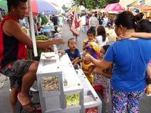 De kinderen kopen suikergoed en snoepjes van een straatventer Stock Afbeeldingen
