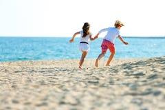 De kinderen koppelen het lopen op strand. Stock Foto's