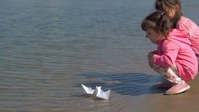 De kinderen laten de boten gaan Meisjes bij de rivier met document boten Twee zusters spelen door het water stock video