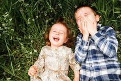 De kinderen liggen in het gras en de lach Royalty-vrije Stock Foto