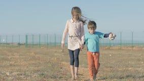 De kinderen lopen dichtbij de staatsgrens Kinderenvluchteling van de landen van oorlogsconflict Behoeftige kinderen blootvoets zo stock videobeelden