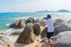 De kinderen lopen en spelen onder grote rotsen op kust op tropische I Stock Foto's