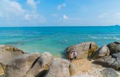 De kinderen lopen en spelen onder grote rotsen op kust op tropische I Royalty-vrije Stock Fotografie