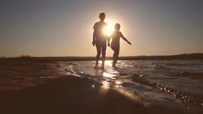 De kinderen lopen langs het strand met hun voeten op het water van de rode avondzonsondergang stock videobeelden
