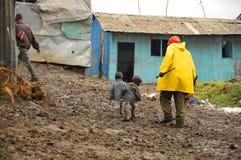 De kinderen lopen in modder stock afbeeldingen