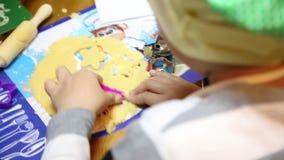De kinderen maken koekjes van hun eigen vorm stock video