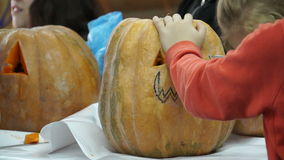 De kinderen maken lantaarns van pompoenen voor Halloween stock footage