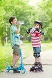 De kinderen met autoped en de rollen drinken water Royalty-vrije Stock Fotografie