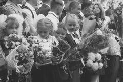 De kinderen met boeketten van bloemen schreven in de eerste klasse met middelbare schoolstudenten in op de schoollijn in de dag v Royalty-vrije Stock Fotografie