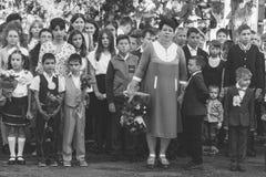 De kinderen met boeketten van bloemen schreven in de eerste klasse in op school op de plechtige lijn in de dag van kennis, zwarte Stock Foto's