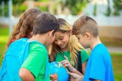 De kinderen met een bol leren aardrijkskunde Stock Afbeeldingen