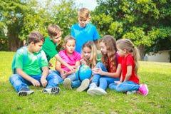 De kinderen met een bol leren aardrijkskunde Royalty-vrije Stock Foto's