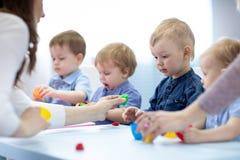 De kinderen met leraar spelen kleurrijk kleistuk speelgoed stock fotografie