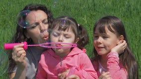 De kinderen met mamma op het groene gras blazen zeepbels Familie in een de zomerpark Mamma en dochters die in aard op s spelen stock footage