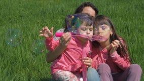 De kinderen met mamma spelen met zeepbels Gelukkige familie op aard in de zomer Meisje met kinderen in het park op een zonnige da stock footage