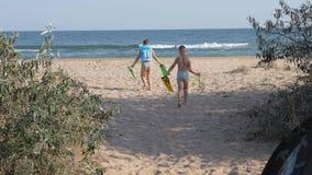 De kinderen met maskers, gaan naar het overzees jongen op het strand in een opblaasbaar vest het kind in de handen van vinnen voo stock footage