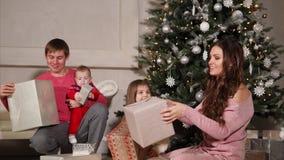 De kinderen met ouders zitten dichtbij grote nieuwe jaarboom en hoop van giften stock video