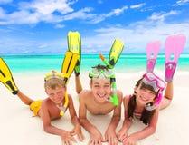 De kinderen met snorkelt door overzees stock foto