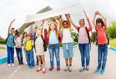 De kinderen met wapens op holding beplakken status stock fotografie