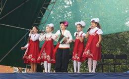 De kinderen in nationaal kostuum zingen op scène bij dag van de stad Stock Afbeeldingen
