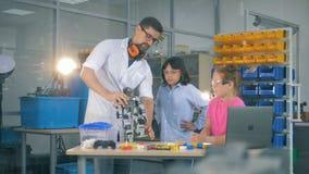 De kinderen nemen een functionerende robot in handen van een laboratoriumarbeider waar stock videobeelden
