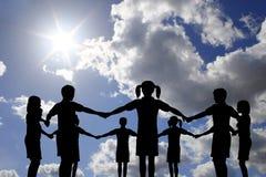 De kinderen omcirkelen op echte zonnige hemel Stock Foto's