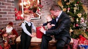 De kinderen ontdekken een gloeiende gift, geeft de vader de zonen van een Kerstmisgift, Kinderen die op giften van ouders, goede  stock videobeelden