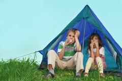 De kinderen op aard, zitten dichtbij tent en eten stock afbeeldingen