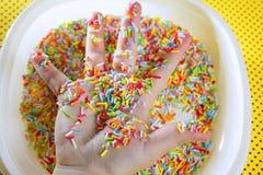 De kinderen overhandigen hoogtepunt van kleine kleurrijke snoepjes stock foto