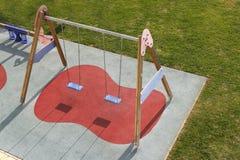 De kinderen parkeren hoge mening van het schommelings de groene gras Royalty-vrije Stock Afbeeldingen