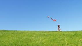 De kinderen reduceren de groene heuvel met een vliegende vlieger stock videobeelden
