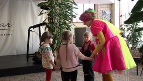 De kinderen` s clown in roze geel kostuum verklaart aan kinderen de regels van het spel en draait hen dans stock video