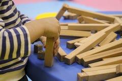De kinderen` s handen verzamelen een houten aannemer het raadsel van het kinderen` s raadsel van houten delen het kind speelt en  stock afbeeldingen