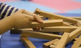 De kinderen` s handen verzamelen een houten aannemer het raadsel van het kinderen` s raadsel van houten delen het kind speelt en  royalty-vrije stock afbeelding