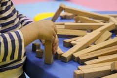 De kinderen` s handen verzamelen een houten aannemer het raadsel van het kinderen` s raadsel van houten delen het kind speelt en  royalty-vrije stock fotografie