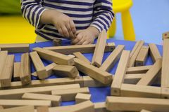 De kinderen` s handen verzamelen een houten aannemer het raadsel van het kinderen` s raadsel van houten delen het kind speelt en  royalty-vrije stock foto's