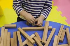 De kinderen` s handen verzamelen een houten aannemer het raadsel van het kinderen` s raadsel van houten delen het kind speelt en  stock foto