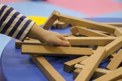 De kinderen` s handen verzamelen een houten aannemer het raadsel van het kinderen` s raadsel van houten delen het kind speelt en  stock fotografie