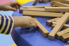De kinderen` s handen verzamelen een houten aannemer het raadsel van het kinderen` s raadsel van houten delen het kind speelt en  royalty-vrije stock foto