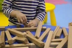 De kinderen` s handen verzamelen een houten aannemer het raadsel van het kinderen` s raadsel van houten delen het kind speelt en  royalty-vrije stock afbeeldingen