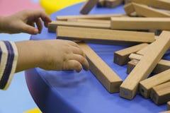 De kinderen` s handen verzamelen een houten aannemer het raadsel van het kinderen` s raadsel van houten delen het kind speelt en  stock afbeelding