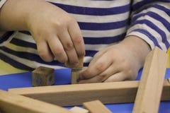 De kinderen` s handen verzamelen een houten aannemer het raadsel van het kinderen` s raadsel van houten delen het kind speelt en  stock foto's