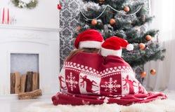 De kinderen in santahoeden dichtbij Kerstmisboom, wachten op vakantie Stock Fotografie