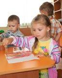 De kinderen schilderen kleuren op papier Stock Afbeelding