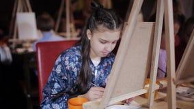 De kinderen schrijven een beeld op canvas in de studio van vroege ontwikkeling Kunststudio voor kinderen stock videobeelden