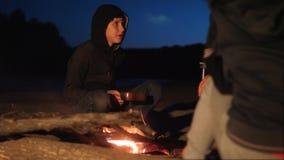 De kinderen silhouetteren jonge geitjestiener zitten door de brand etend popcorn bij nachtkampvuur reis wandelingsavontuur het ka stock videobeelden