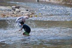 De kinderen spelen bespattend water in de natuurlijke kreek royalty-vrije stock foto's