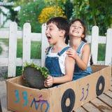 De kinderen spelen in de auto Stock Afbeeldingen